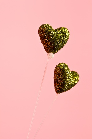 two glittering green heart made by styrofoam on pink background in portrait orientation photo