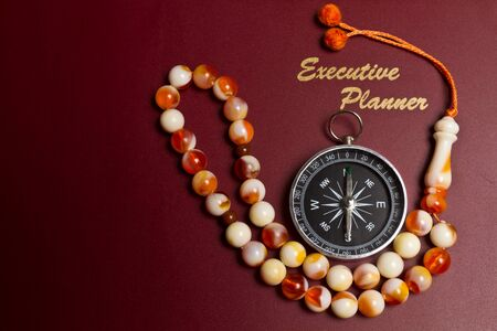 dark red executive planner with rosary beads in landscape orientation photo