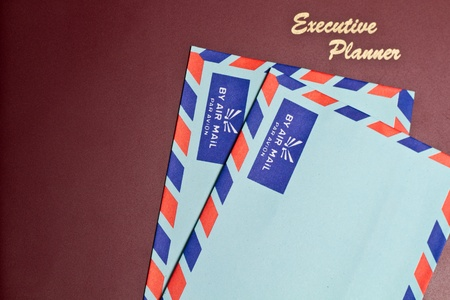 a dark red executive planner with two blue color envelopes photo