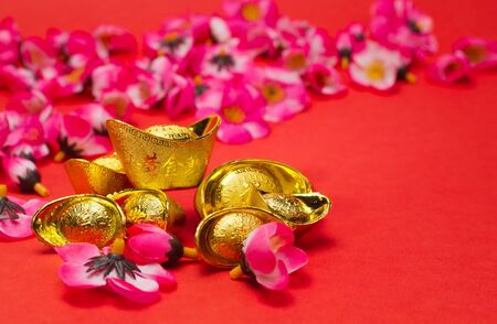 Golden Ingots with plum blosoms on red surface and background for Chinese New Year usage Stock Photo - 11842164