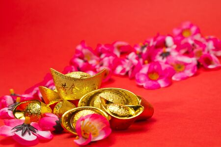 whit: Golden Ingots whit plum blosoms on red surface and background for Chinese New Year usage