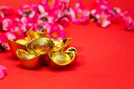 Golden Chinese New Year Ingots on red surface with plum blossoms in background Stock Photo