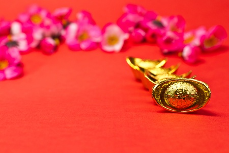 Golden Chinese new Year Ingots on red surface with plum blossoms in background photo