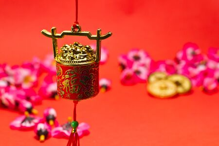 Chinese New Year ornament on red background with cherry blossom and gold coins for festive using photo