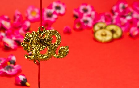 Chinese New Year dragon ornament on red background with cherry blossom for festive using photo