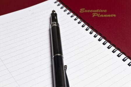 a brown executive planner with spiral note book and a pen in lanscape orientation photo