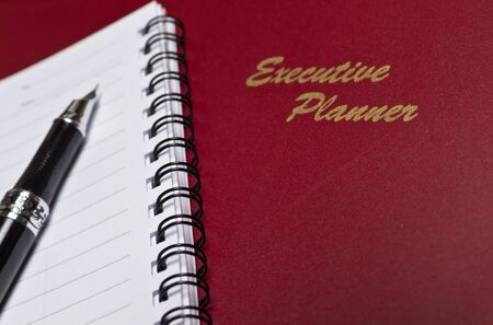 angled view of a  marron executive planner with spiral note book and a pen in lanscape orientation photo
