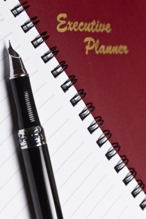 angled view of a marroon executive planner with spiral note book and a pen in portrait orientation photo