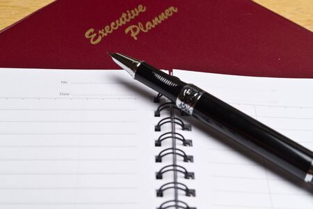 angled view of a  dark red executive planner with spiral note book and a pen in lanscape orientation photo
