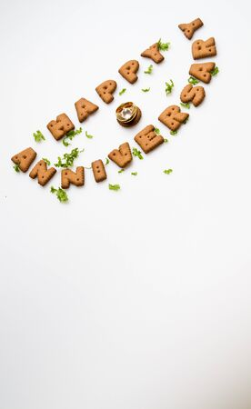 Happy anniversary wording by brown biscuits, diamond ring and green leaves on white surface slanting position photo