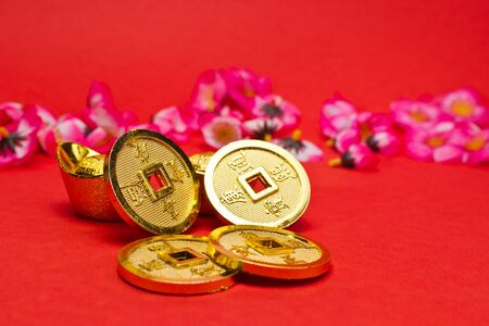 Golden nuggets and emperors coins with cherry plum blossoms on red surface for Chinese New Year Stock Photo - 11920012