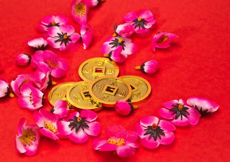 Golden coins ornaments with plastic cherry blossoms on red surface for CNY celebration photo