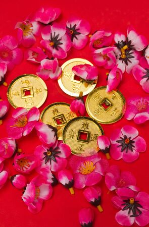 Golden coins ornaments with plastic cherry blossoms on red surface for CNY celebration in portrait orientation Stock Photo