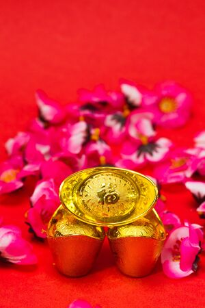 usage: 3 Chinese Golden Ingots with plum blosoms on red surface and background for Chinese New Year usage
