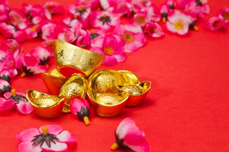 Golden Ingots with plum blosoms on red surface and background for Chinese New Year usage photo