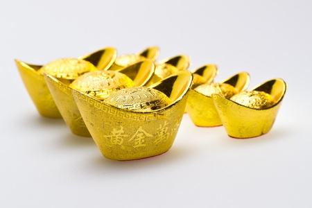 fa: Chinese gold Ingots of various size line up on white surface