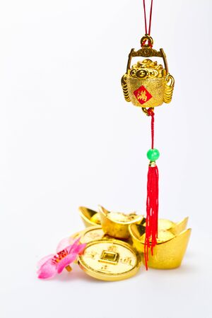 Hanging wealth pot pendant for Chinese New Year celebration with gold ingots and coins in background against white surface