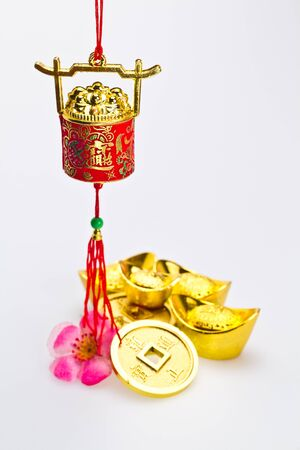 Hanging red wealth pot with gold igots and coins on white surface in portrait orientation