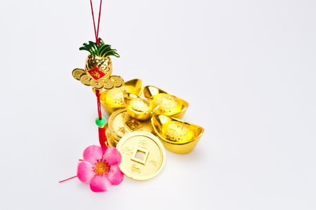fa: Golden ineapple for chinese new yer celebration with ingots and coins against white surface