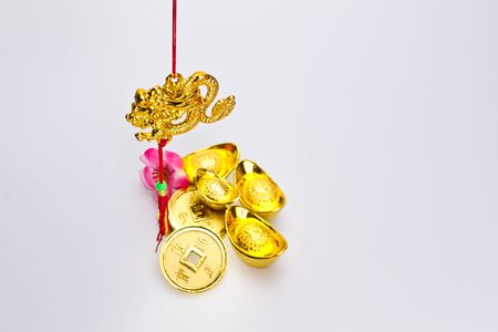 prosperous: Angled view of hanging golden dragon with god ingots and coins against white background Stock Photo