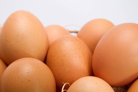Close up view of brown table eggs in metal basket with straw bedding Stock Photo