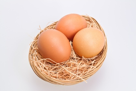 Three brown eggs in rattan basket with straw bedding on white background