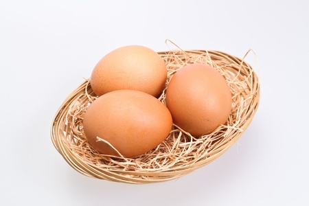 Angled view of three brown eggs in rattan basket with straw bedding on white background photo