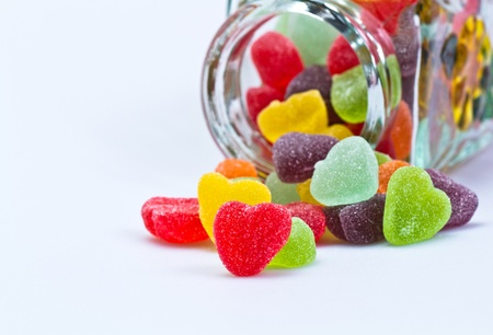 colourful candy: close up view of love-shaped jelly spilled from a glass container on white surface