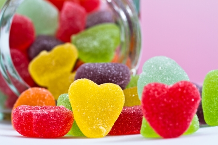 close up view of a yellow love-shaped jelly spilled from a glass container on pink background