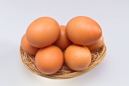 brown eggs in rattan basket isolated on whte surface