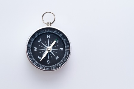 a simple metal compass hanged on white surface with copy space Stock Photo