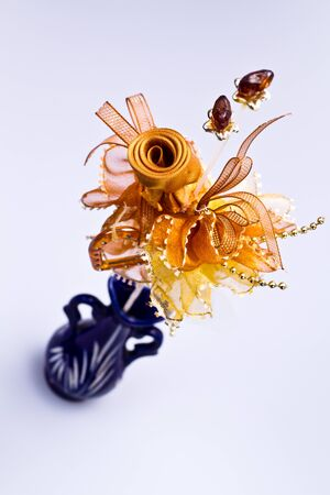 angled view: Angled view of a brown flower made by ribbon in blue vase on white background in portrait orientation