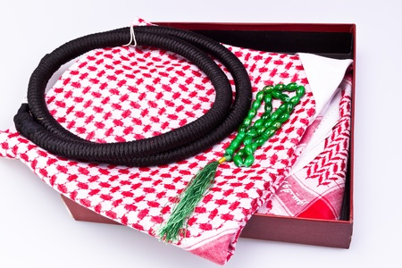 folded muslim head gear with rosary bead in gift box on white surface photo