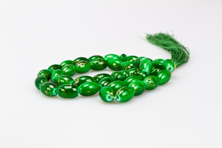 green rosary beads on white background