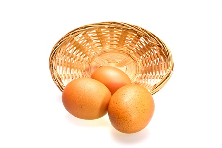 close up view of three brown eggs in rattan basket on white surface photo