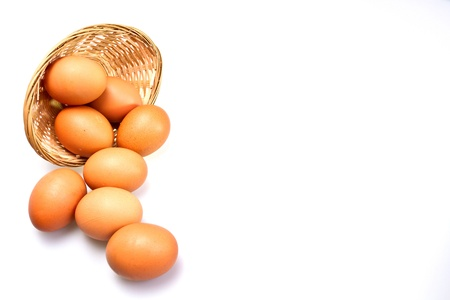 Brown eggs and rattan basket on white surface with copy space for frame use photo
