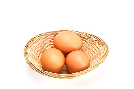 three brown eggs in rattan basket on white surface landscape orientation