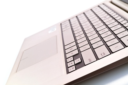 Angled view of a keyboardpad on a modern laptop against white for abstract and background photo