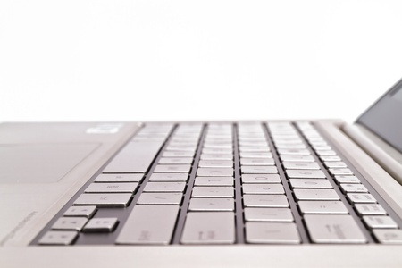 Angled view of a keyboardpad on a modern metal-finished laptop against white for abstract and background Stock Photo
