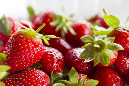 close up view of bunch of strawberries on white plastic plate with natural lighting Stock Photo