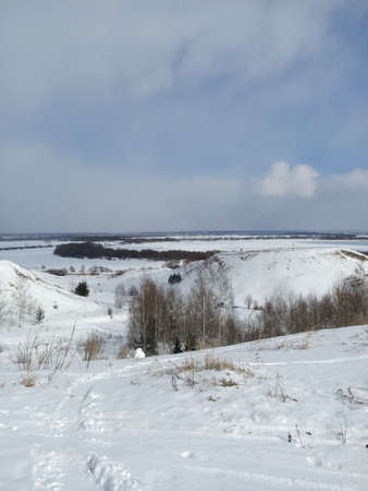 Winter snow on the water field of the river ice and on banks hills under white clouds in blue sky Foto de archivo