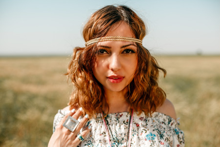 portrait of a young hippie girl on a wheat field