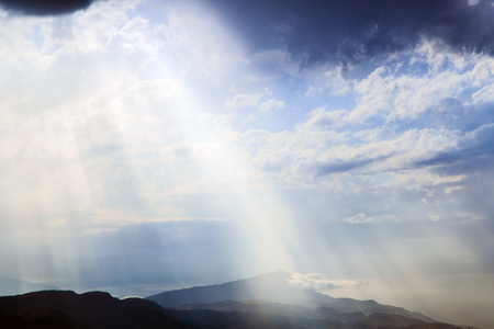 The suns rays make their way through the clouds. background 写真素材