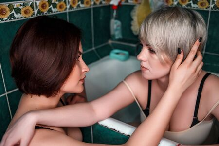 blonde with brunette in bathroom in underwear touch each other and experience feelings