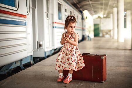 little cute Caucasian girl in vintage clothes with vintage suitcase at small railway station