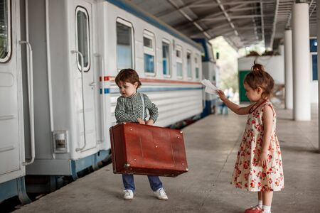 little boy and girl in vintage clothes with vintage suitcase at small railway station