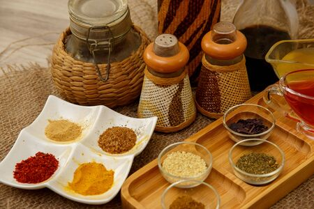 different types of spices in different containers on wood and canvas Stok Fotoğraf