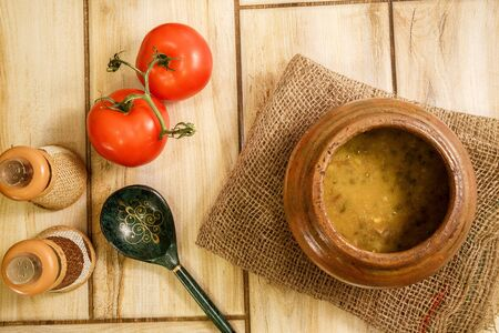 Bean soup in a traditional pot on a wooden background. View from above. Archivio Fotografico