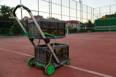trolley for tennis balls on the tennis court in the evening