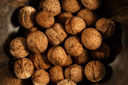 walnuts on a wooden table and in iron utensils